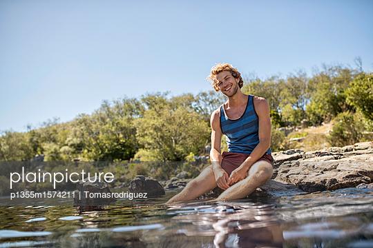 Junger Mann badet seine Füße im Fluss - p1355m1574211 von Tomasrodriguez