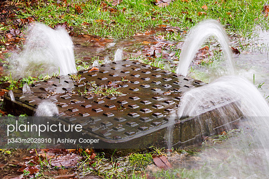 A man hole cover being pushed up under the force of water pressure during flooding in Ambleside, Lake District, Cumbria, UK - p343m2028910 by Ashley Cooper