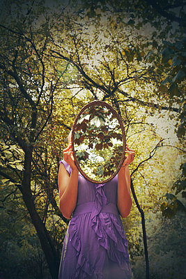 Woman covering face with mirror in woods - p1248m2008577 by miguel sobreira