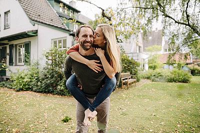 Woman kissing man, carrying her piggyback in garden - p300m2166678 by Kniel Synnatzschke