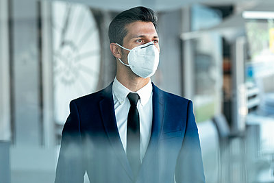 Businessman wearing protective face mask looking away while standing in office - p300m2256009 by Josep Suria