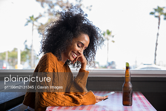 Adult black woman texting and enjoying beer in a California restaurant - p1166m2131345 by Cavan Images