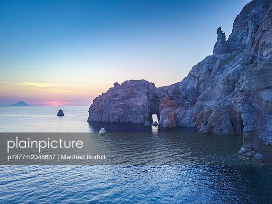 Italy, Sicily, Messina district, Mediterranean sea, Tyrrhenian sea, Tyrrhenian coast, Aeolian islands, Vulcano, Sunset from the area of faraglioni rocks in Lipari with Filicudi island on the background - p1377m2048837 by Manfred Bortoli