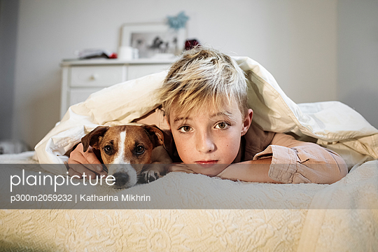 Portrait of blond boy and his Jack Russel Terrier lying together on bed - p300m2059232 von Katharina Mikhrin