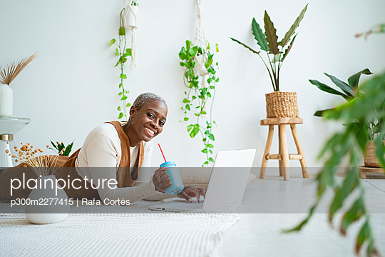 Smiling female entrepreneur holding jar while lying in front of laptop at home - p300m2277415 by Rafa Cortés