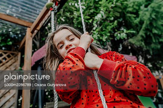 portrait of a girl riding a swing in a garden, Berlin, Germany - p300m2286789 von Oxana Guryanova