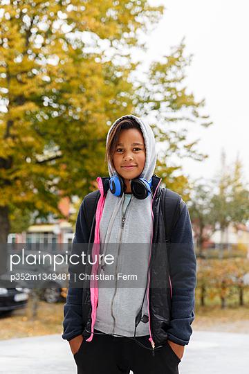Sweden, Sodermanland, Jarna, Portrait of girl (12-13) with headphones and hood on