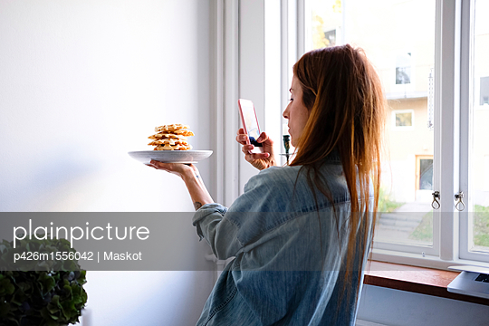 Woman photographing waffles through smart phone in plate by wall at home - p426m1556042 by Maskot