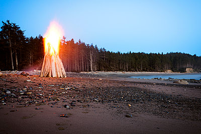 Bonfire at seashore against clear sky - p1166m1154154 by Cavan Images
