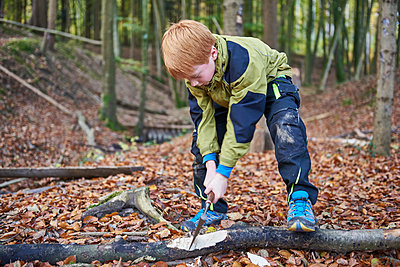 Boy chopping wood in forest - p300m1417031 by Jess Derboven