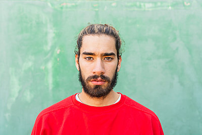 Portrait of bearded young man wearing red sweatshirt in front of green wall - p300m2159951 by VITTA GALLERY