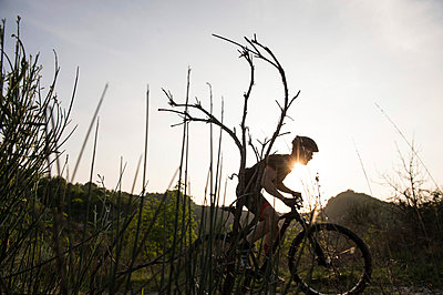 Man riding mountain bike in nature in the Bologna countryside, Italy - p307m937557f by Enrico Calderoni