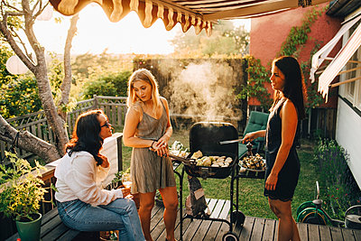 Friends talking while grilling food on barbecue for dinner party in yard - p426m2097499 by Maskot