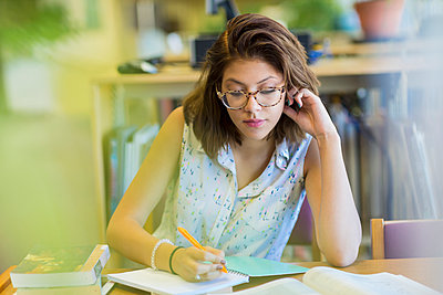Mixed Race girl studying in library - p555m1302105 by Marc Romanelli