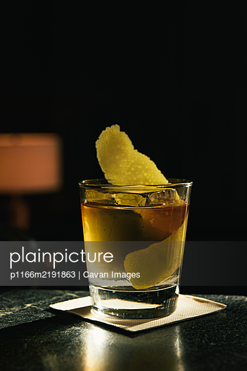 Old fashioned cocktail with citrus in sun beam at bar top - p1166m2191863 by Cavan Images
