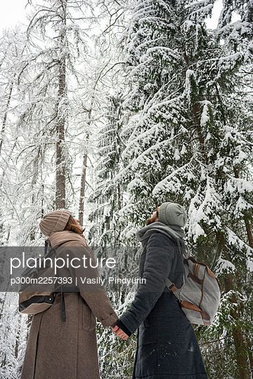 Couple looking at snowy trees while standing in forest - p300m2257393 by Vasily Pindyurin