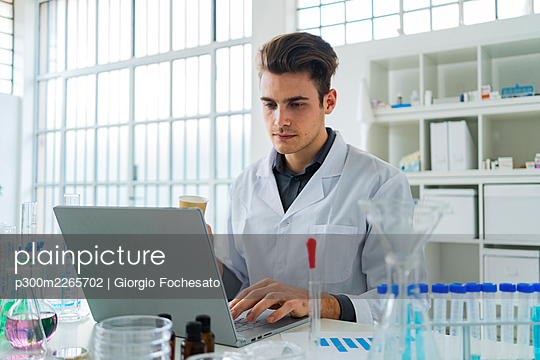 Serious male scientist working on laptop while sitting at desk in laboratory - p300m2265702 by Giorgio Fochesato