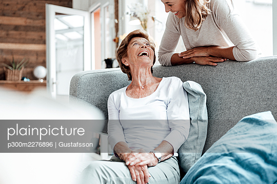 Laughing grandmother looking at granddaughter leaning on sofa - p300m2276896 by Gustafsson