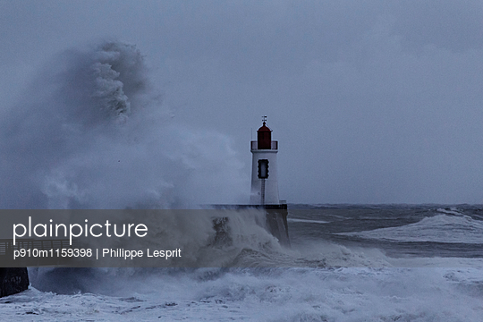 Lighthouse with surging billows - p910m1159398 by Philippe Lesprit