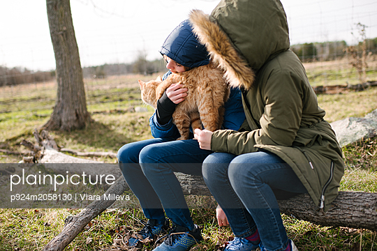 Brother and sister cuddling cat in field - p924m2058130 by Viara Mileva