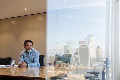 Thoughtful businessman in highrise conference room, London, UK - p1023m2212565 by Martin Barraud