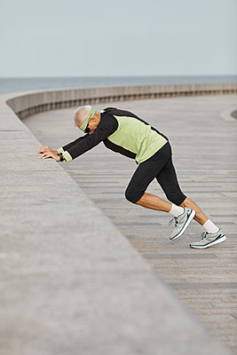 Man Wearing Sporty Outfit Exercising At Seafront - p1166m2147042 by Cavan Images