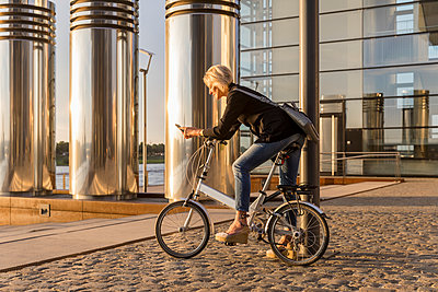 Senior woman with city bike using cell phone at the riverside at sunset - p300m2004768 by Jo Kirchherr