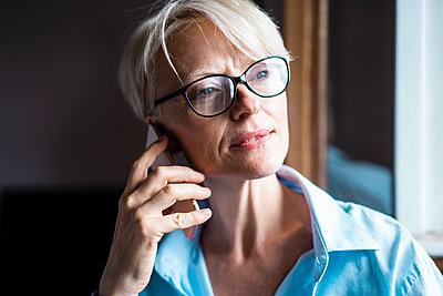 Businesswoman with eyeglasses looking away while talking on mobile phone in home office - p300m2267755 by Robijn Page