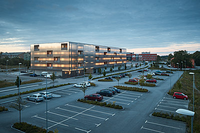 Modern residential building and parking lot at dusk - p312m1470897 by Johan Alp