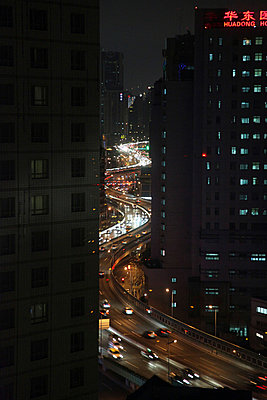 Night highway between buildings - p664m788111 by Yom Lam