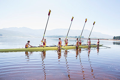Rowing team with oars raised on lake - p1023m923578f by Chris Ryan