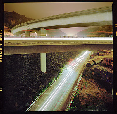 Lights trails on overpass by mountain during sunset - p1166m1194009 by Cavan Images