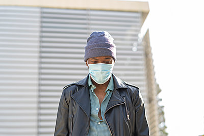 young african man walking through the city wearing the mask - p1166m2218238 by Cavan Images
