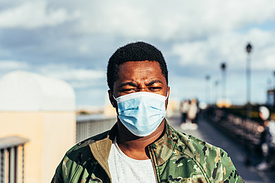 Portrait of a black boy with face mask. Dressed in military jacket. - p1166m2254927 by Cavan Images