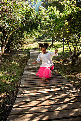 Little girl walking on planked footpath - p1640m2246843 by Holly & John