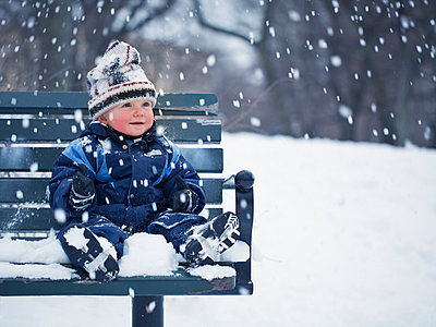 Baby boy sitting on bench and looking at falling snow - p312m1076149f by Matilda Lindeblad
