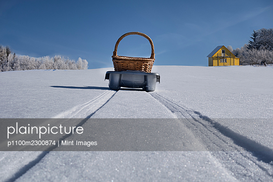 Sled transporting basket over hilly snowy winter landscape, Estonia - p1100m2300874 by Mint Images