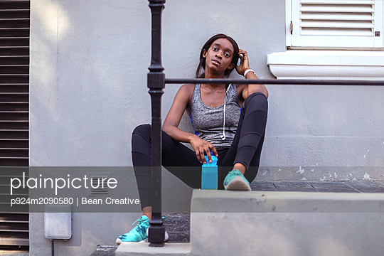 Young female runner sitting on city sidewalk stairs, portrait - p924m2090580 by Bean Creative