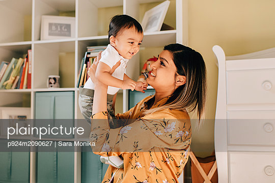 Mother holding up baby son in nursery - p924m2090627 by Sara Monika