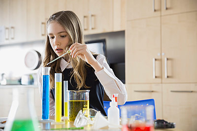 School girl conducting experiment in science classroom - p1192m1023982f by Hero Images