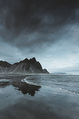 Sharp mountain and a black sand beach in East Iceland - p1634m2210392 by Dani Guindo