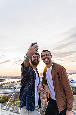 Gay couple taking a selfie on lookout above the city with view to the port, Barcelona, Spain - p300m2155146 by VITTA GALLERY