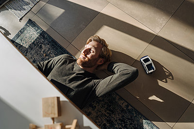 Relaxed man lying on the floor at home - p300m2167237 by Kniel Synnatzschke