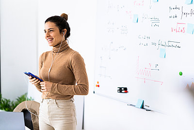 Female student or worker in front of a board with mathematical & physical formulas - p300m2242588 von Giorgio Fochesato