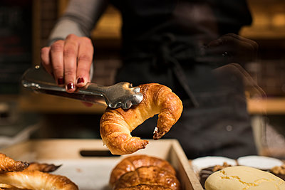 Young baker holding croissant in serving tongs at bakery - p300m2265007 by David Agüero Muñoz