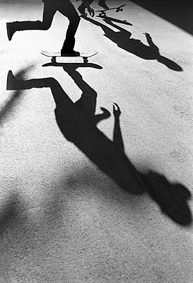 Silhouetted skateboarders - p301m744374f by Brian Caissie