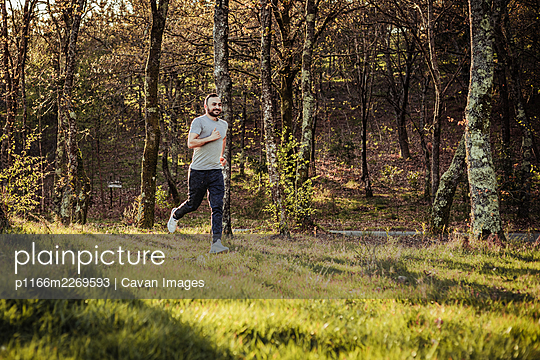 Man in cap and dark tracksuit running through the forest - p1166m2269593 by Cavan Images