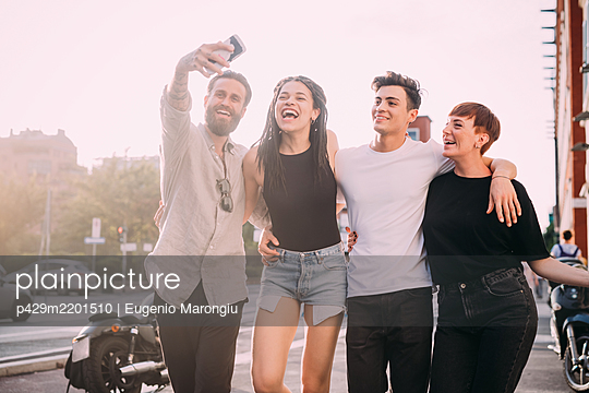 Two young women and men wearing casual clothes standing on a rooftop, taking selfie with mobile phone. - p429m2201510 by Eugenio Marongiu