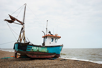 Blue fishing boat lying on pebble beach near the water's edge, Aldeburgh, Suffolk, England. - p1100m1490122 by Mint Images