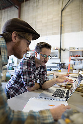 Male design professional engineers meeting at laptop at workbench in workshop - p1192m1202138 by Hero Images